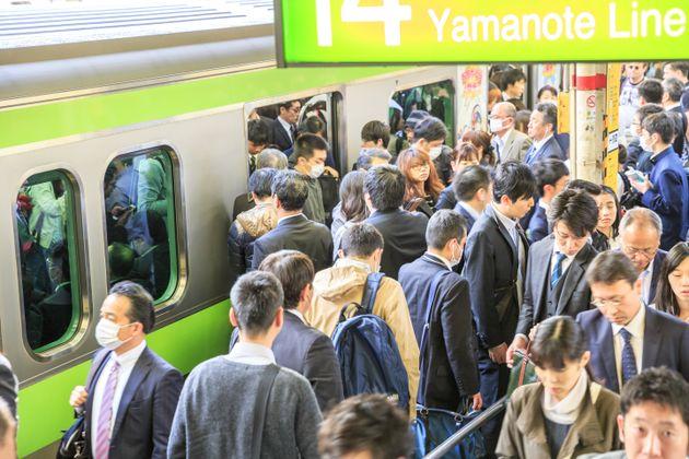 通勤時、満員電車に乗り込む人々
