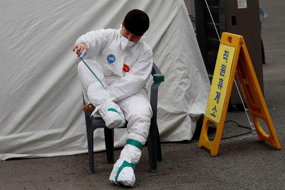 한 소방대원이 환자 이송을 위해 보호복을 착용하고 있다. 대구. 2020년