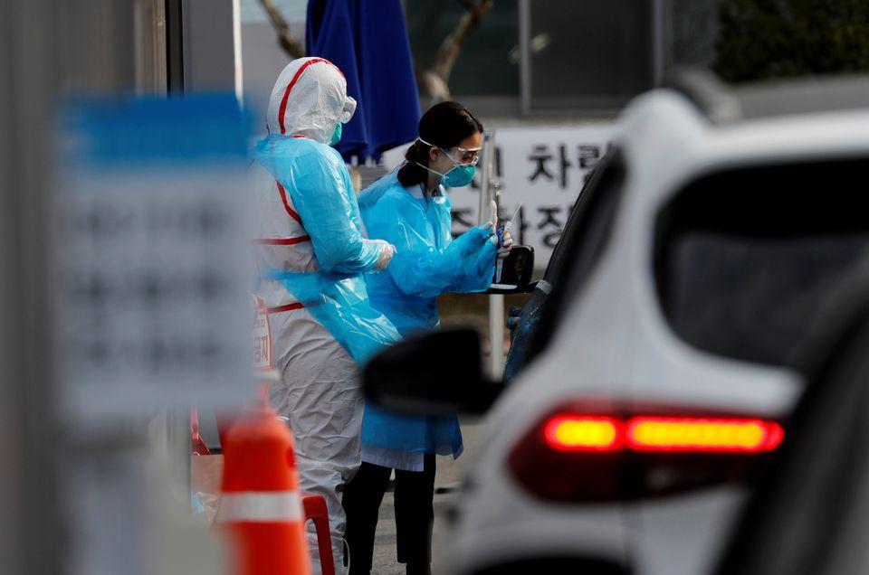 의료진들이 영남대학교병원 '드라이브 스루' 선별진료소에서 환자들의 검체를 체취하고 있다. 대구. 2020년