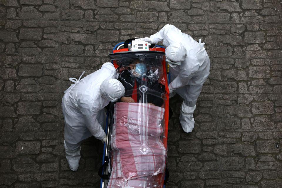 의료진이 음압들것에 실려 이송된 환자를 병원 안으로 옮기고 있다. 서울. 2020년
