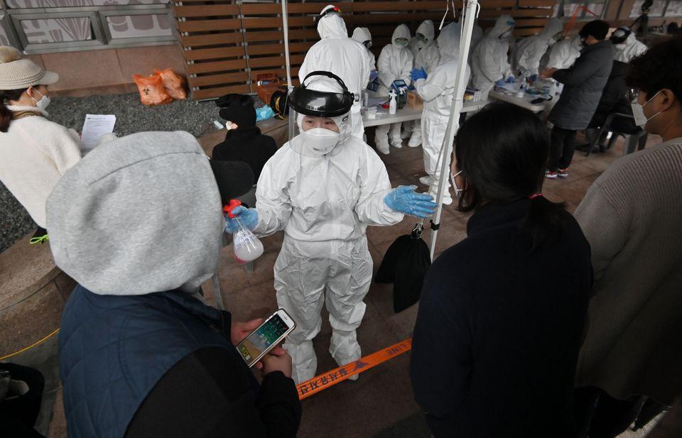 집단 감염이 발생한 서울시 구로구의 한 콜센터 앞에 설치된 임시 선별진료소에서 의료진이 빌딩에서 일하는 직원들에게 안내사항을 전달하고 있다. 서울.