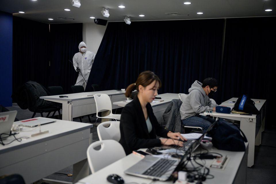 방역당국의 언론 브리핑이 진행되는 기자실에서 한 방역요원이 방역작업을 벌이고 있다. 서울. 2020년