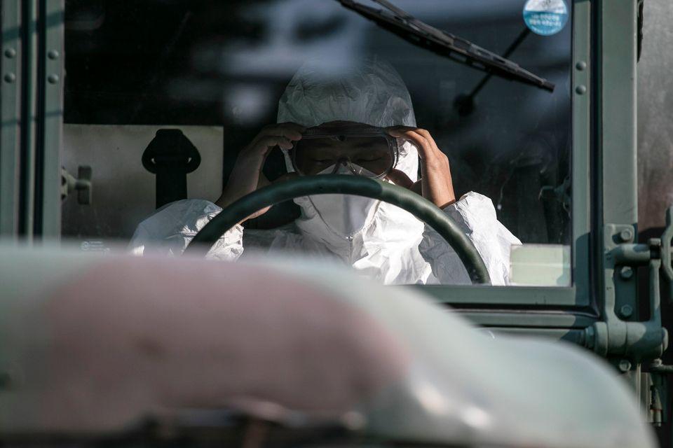 서울 은평구 일대 방역작업에 투입된 한 군 운전병이 보호장구를 고쳐쓰고 있다. 서울. 2020년
