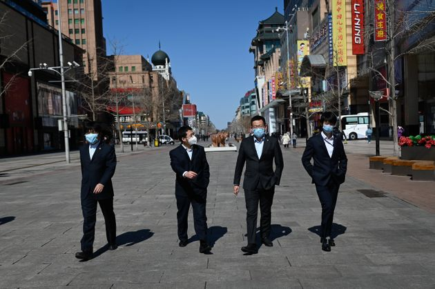 A group of people wearing face masks walk along a street in Beijing on March 10, 2020. - The soaring...