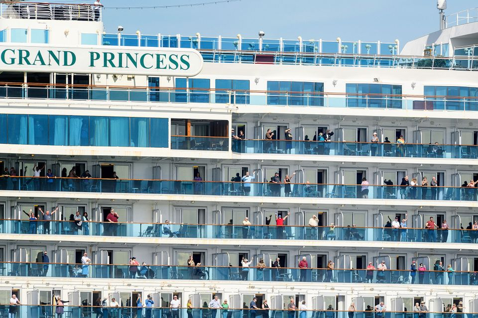 Passengers aboard the Grand Princess celebrate as they arrive in Oakland,