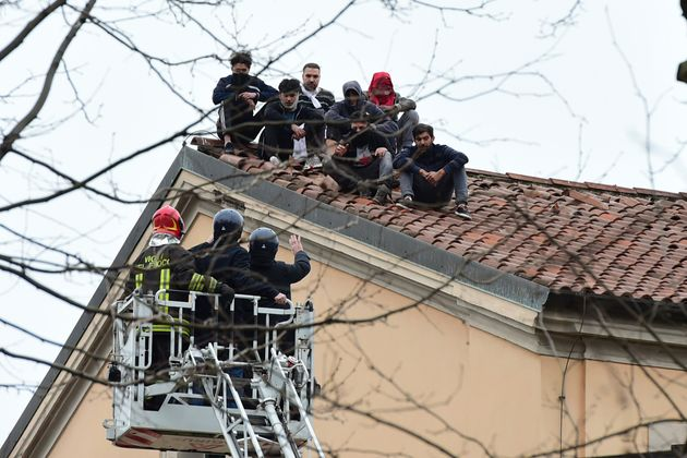 MILAN, ITALY - MARCH 09: Prisoners of the San Vittore Prison speak with the police, on the roof during...