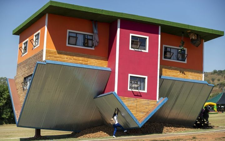 A visitor pretends to hold the structure up at the upside-down house in Hartbeespoort, South Africa.