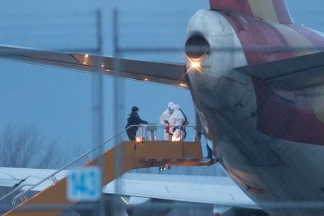Staff in protective suits help a passenger step off a plane at Canadian Forces Base Trenton in Trenton,...