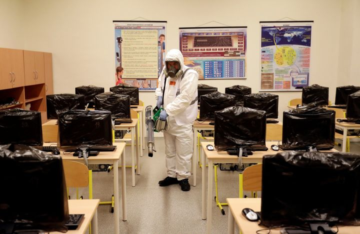 A worker in a protective suit disinfects a classroom inside of an elementary school due to coronavirus concerns in Prague, Cz