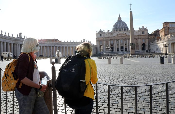 People stand behind barriers on Tuesday after the Vatican's Saint Peter's Square and its main basilica were closed to tourist
