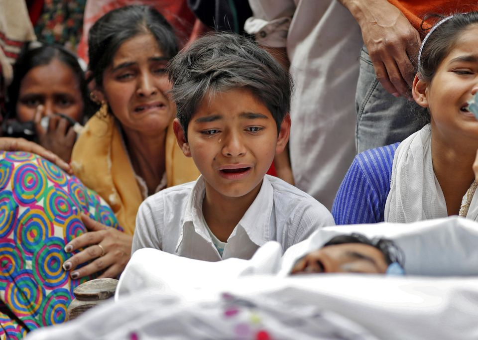 People mourn next to the body of Muddasir Khan, who was wounded during the communal violence that occurred...