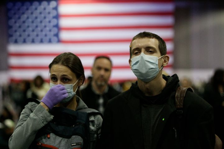 Alaina Marasa (left) and Tobias Riker of La Mirada, California, wear face masks and gloves at a Los Angeles campaign event for Democratic presidential candidate Sen. Bernie Sanders (I-Vt.) on Sunday.