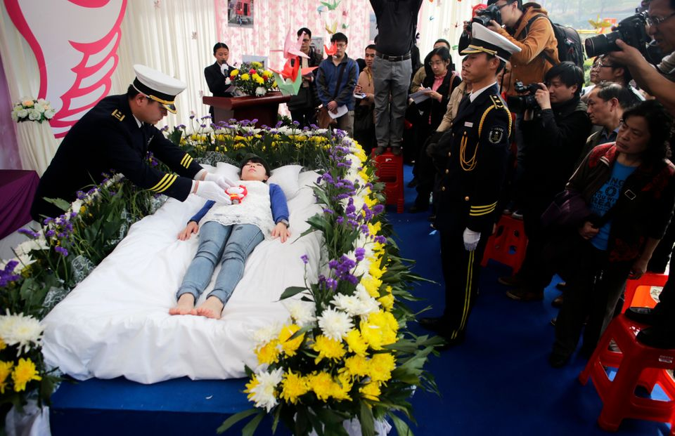 People pay tribute to Zeng Jia (center lying) at her faux funeral in Wuhan city, central Chinas Hubei province, 30 March 2013
