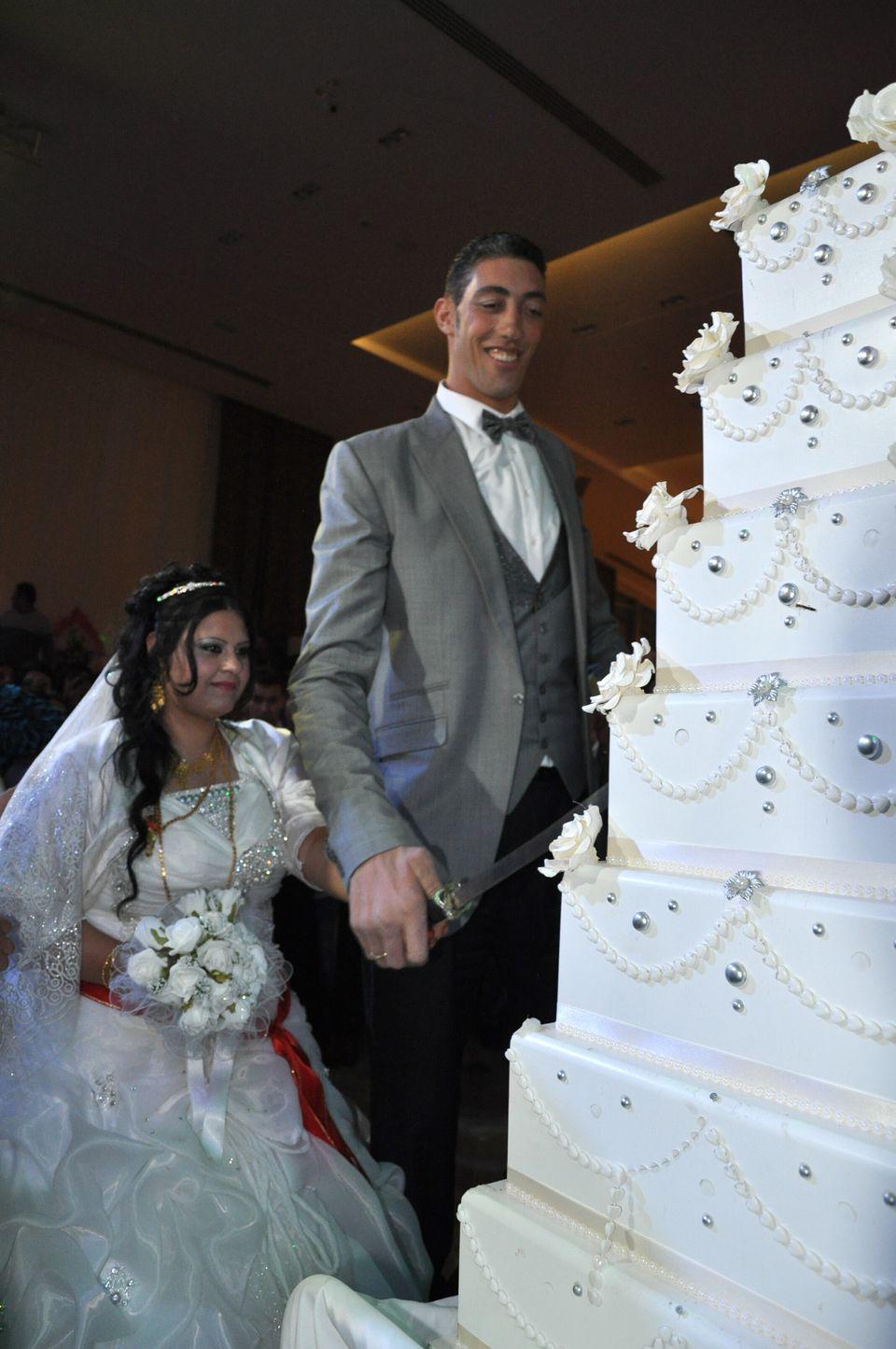 The world's tallest man Sultan Kosen (R) and his bride cut their wedding cake on October 27, 2013 in Mardin during their wedd