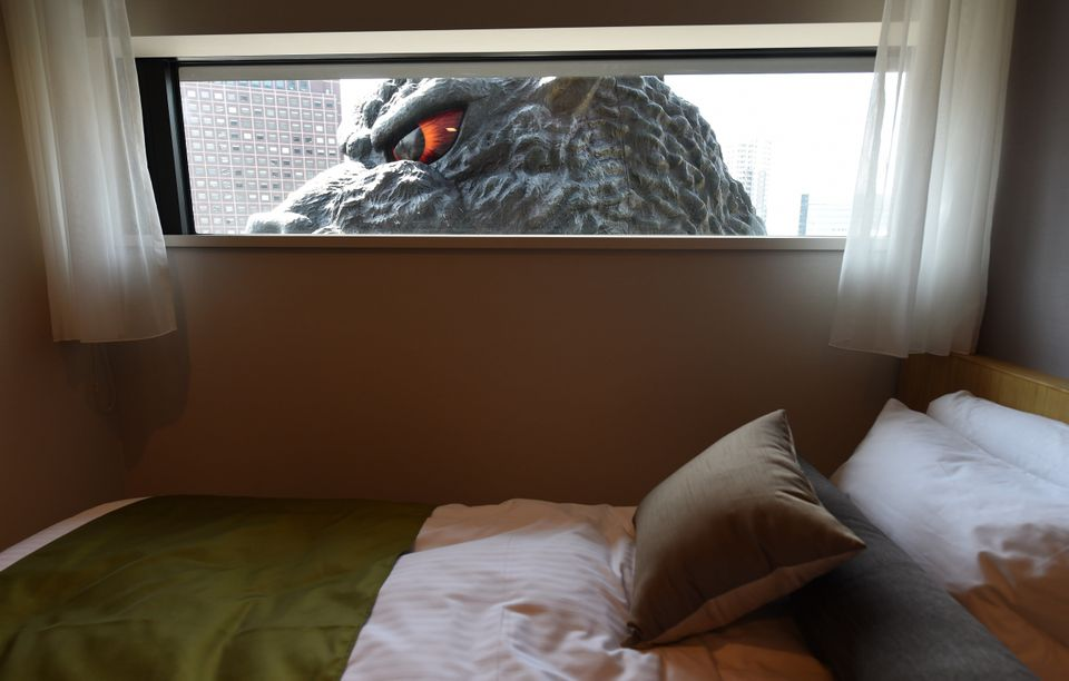 A life-size Godzilla head is seen through a window of the 'Gozilla View Room' of Hotel Gracery Shinjuku at Kabukicho shopping