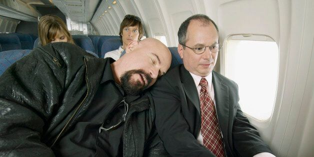 Man Sleeping on a Plane With His Head Resting on a Businessman's Shoulder