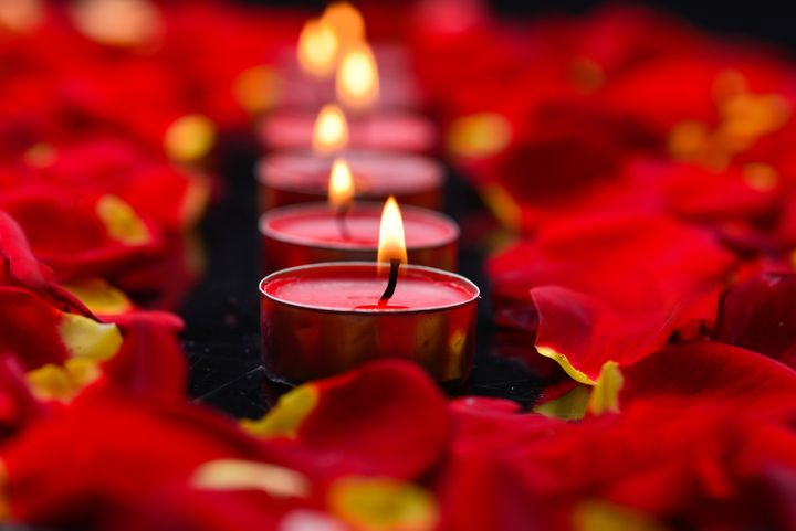 red candles with rose petals in ...