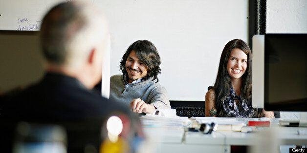 Coworkers sitting at workstation in high tech startup office in discussion with mature businessman laughing