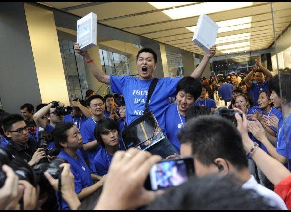 Apple customer Han Ziwen shouts holding his ipads outside Apple's flagship store in Beijing after queuing for 60 hours to be