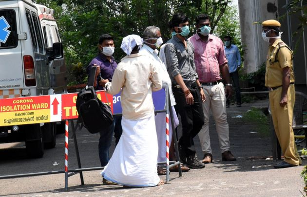 People are seen wearing masks outside the special isolation ward set up to provide treatment to novel...