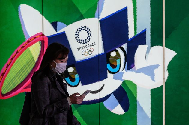 A woman wearing a face mask walks in the tunnel of a metro station with a poster of Miraitowa, official...