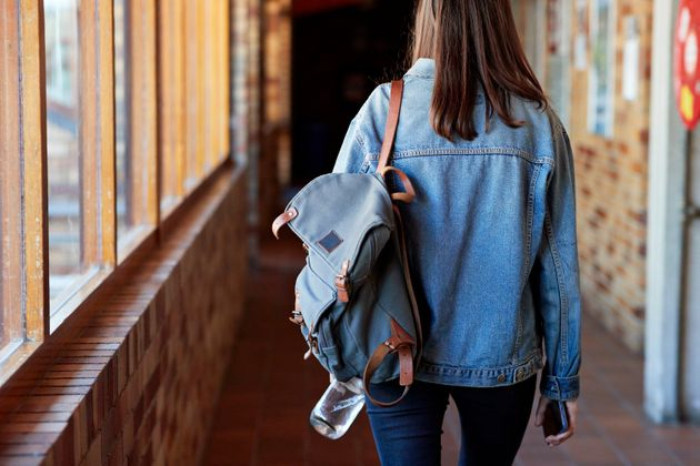 Rear view of young woman with backpack walking in corridor at