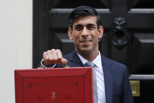Rishi Sunak stands outside No 11 Downing Street and holds up the traditional red box that contains the budget speech for the media.