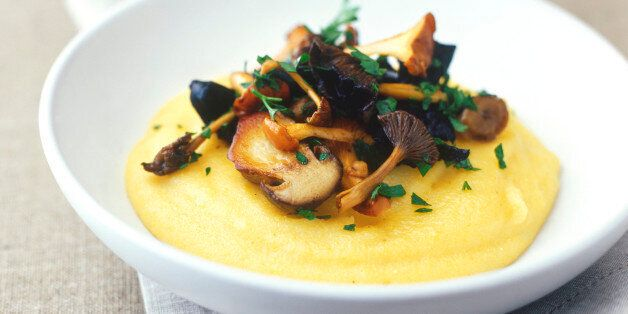 Dish of soft polenta topped with sauteed wild mushrooms garnished with parsley