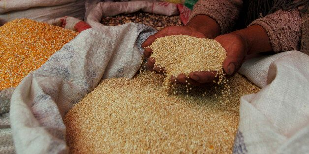 """A woman shows her quinoa grain for sale at a market in La Paz, Bolivia, Friday March 2, 2012.  Bolivian authorities say at least 30 people have been injured in a fight between two communities over land for growing quinoa, the Andean """"super-grain"""" whose popularity with worldwide foodies has caused its price to soar. Bolivia produces 46 percent of the world's quinoa, which has nearly tripled in price in the past five years. (AP Photo/Juan Karita)"""