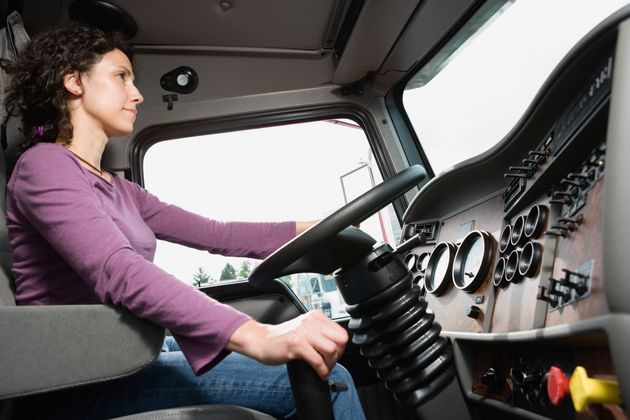 In this stock photo of the interior of a truck, a woman is seen at the steering