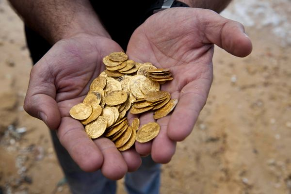Kobi Sharvit of the Israel Antiquities Authority holding the Fatimid-period gold coins that were found in the seabed in the M