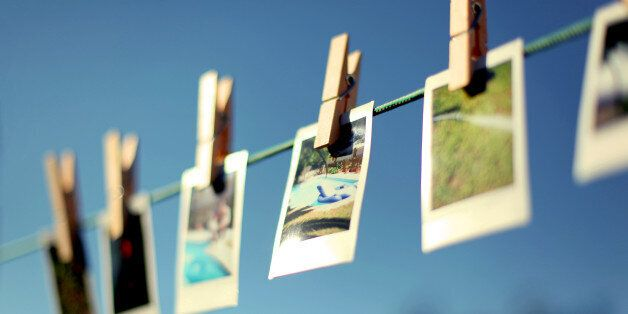 Summery pictures hanging from washing line using clothespins.