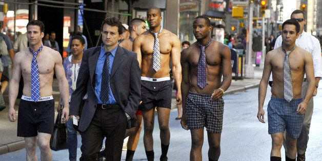 Male models in the underwear follow men in suits around Times Square June 27, 2012 to promote the Men's Wearhouse national su