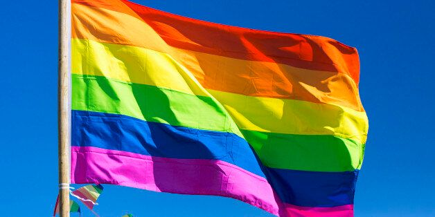 Rainbow flag against sky during gay pride parade