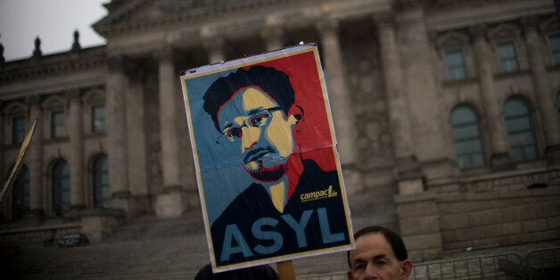 Campact activists hold up a portrait of US whistleblower Edward Snowden in front of the Reichstag building housing the Bundes