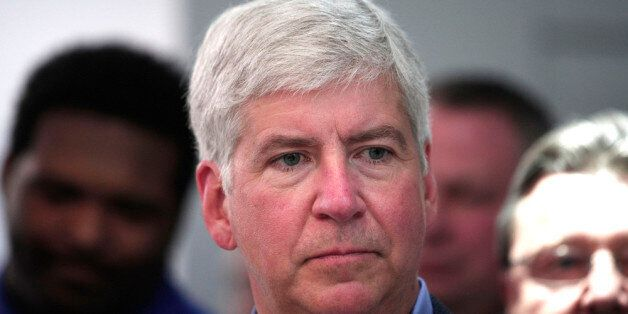 DETROIT, MI - JANUARY 14: Michigan Gov. Rick Snyder visits the Denso display to talk about Michigan and automatic vehicle tec