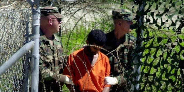 Guantanamo Bay, CUBA:  (FILES) This 02 March, 2002, file photo shows a detainee escorted by two US Army MPs at Camp X-Ray in