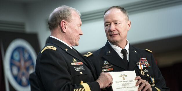 Chairman of the Join Chief of Staff Army General Martin Dempsey (L) presents General Keith B. Alexander with a certificate af