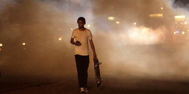 FERGUSON, MO - AUGUST 17 : A man with a skateboard protesting Michael Brown's murder walks away from tear gas released by pol