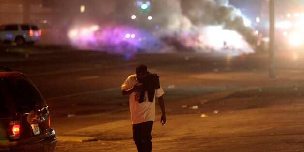 FERGUSON, MO - AUGUST 17 : A man protesting Michael Brown's murder walks away from tear gas released by police August 17, 201