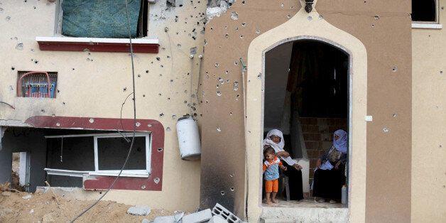 GAZA CITY, GAZA - AUGUST 17: Palestinian women sit among the debris of a building destroyed in Israeli shelling in Johr al-De