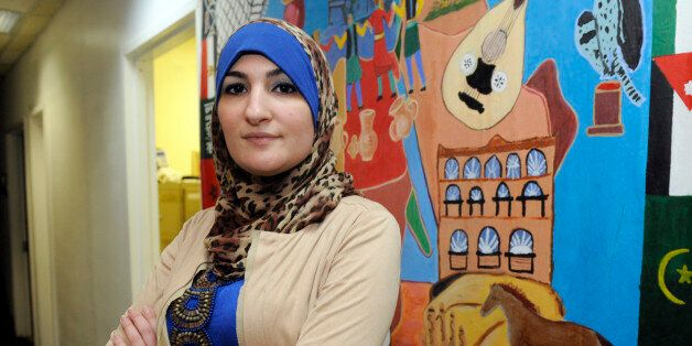 Linda Sarsour, director of the Arab American Association of New York, poses for photos in front of a canvas painted by the as