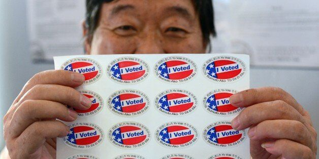 Election official Henry Tung displays a sheet of 'I Voted' stickers in various  languages at a polling station at St. Paul's