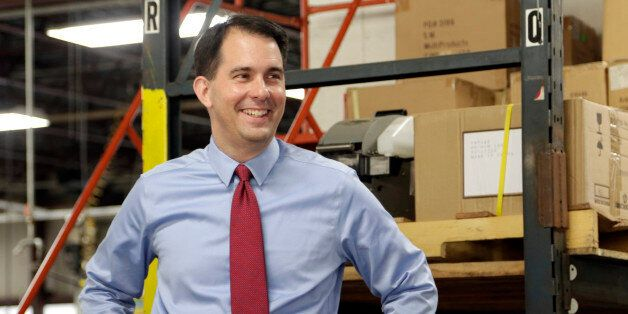 In this Sept. 23, 2014 photo Republican Wisconsin Gov. Scott Walker campaigns for re-election at a manufacturing company in R