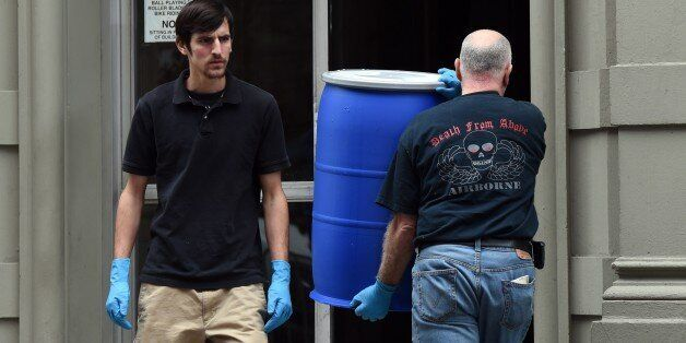 Hazmat crews take barrels into the apartment building of Dr. Craig Spencer, a member of Doctors Without Borders, October 24,