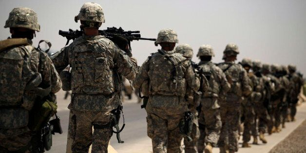 In this Tuesday, Aug. 2, 2011 photo, U.S. Army soldiers make their way to a C-130 aircraft at Sather Air Base in Baghdad, Ira