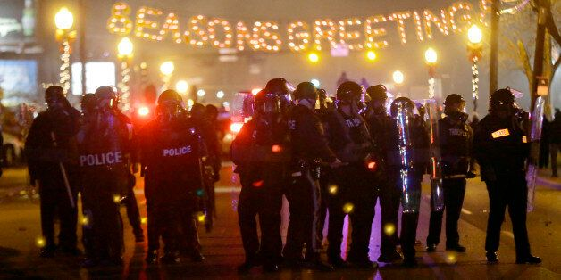 Police gather on the street as protesters react after the announcement of the grand jury decision Monday, Nov. 24, 2014, in F