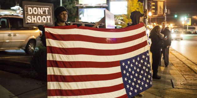 FERGUSON, MO - OCTOBER 10 :   Protestors hold an American flag upside down, universal sign for distress, outside the Ferguson