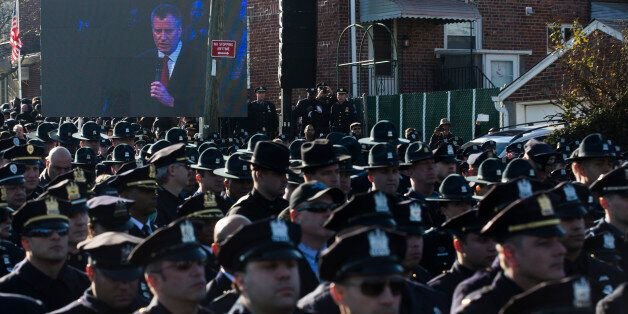Police officers turn their backs as New York City Mayor Bill de Blasio speaks at the funeral of New York city police officer