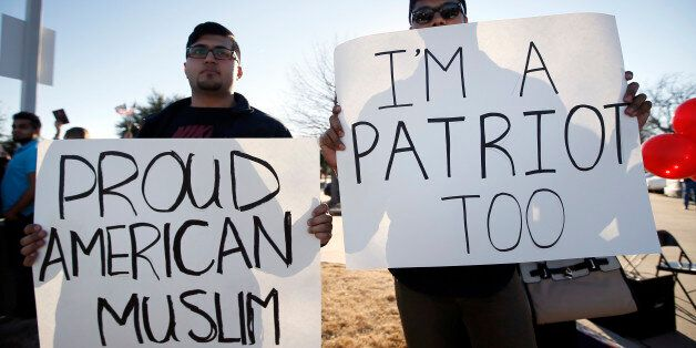 Sharjeel Hassan, left, and Yusuf  Alwar,, both of Richardson, Texas, holds signs as they stand with supporters outside the Cu